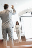 Cheerful businesswoman with luggage walking towards male colleague in convention center Royalty Free Stock Images