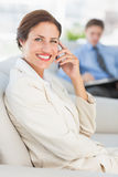 Cheerful businesswoman on the phone sitting on couch Stock Photos
