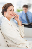Cheerful businesswoman on the phone sitting on sofa Stock Images