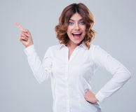 Cheerful businesswoman pointing finger away Stock Images