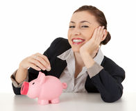 Cheerful businesswoman putting coin to piggybank Royalty Free Stock Photography