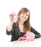 Cheerful businesswoman putting coin to piggybank Stock Photos