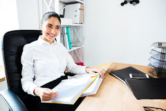 Cheerful businesswoman reading documents while sitting at the office desk Stock Photo