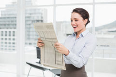 Cheerful businesswoman reading newspaper in office Stock Photo