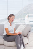 Cheerful businesswoman relaxing and reading newspaper Royalty Free Stock Images