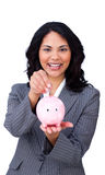 Cheerful businesswoman saving money in a piggybank Stock Photography