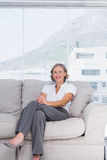 Cheerful businesswoman sitting on couch Royalty Free Stock Photo