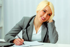 Cheerful businesswoman sitting at the table on her workplace Stock Images