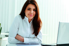 Cheerful businesswoman sitting at the table on her workplace Stock Photo