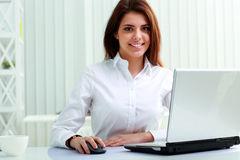 Cheerful businesswoman sitting at the table on her workplace Stock Photography