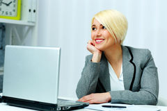 Cheerful businesswoman sitting at the table with laptop Royalty Free Stock Photo