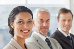 Cheerful businesswoman smiling with colleagues behind Royalty Free Stock Photography