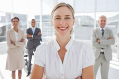Cheerful businesswoman standing with arms folded Stock Images