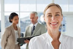 Cheerful businesswoman standing with colleagues working behind Stock Photos
