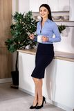 Cheerful businesswoman standing in the kitchen royalty free stock image