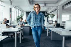 Cheerful businesswoman standing in office environment royalty free stock photography