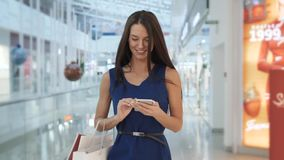 Cheerful businesswoman texting on smart phone while waiting for her flight in airport terminal. shopping mall woman talk. Cheerful businesswoman texting on smart stock footage