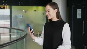 Cheerful businesswoman texting on smart phone while waiting for her flight in airport terminal happy smiling girl model. Cheerful businesswoman texting on smart stock video
