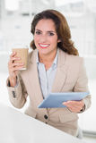 Cheerful businesswoman using digital tablet at her desk holding disposable cup Stock Image