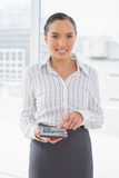 Cheerful businesswoman using her calculator Stock Photos