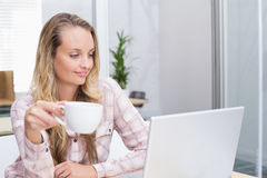Cheerful businesswoman using her notebook holding a cup Stock Photography