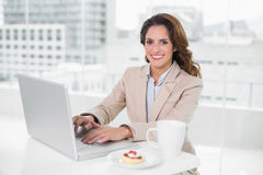 Cheerful businesswoman using laptop at her desk and having coffee Royalty Free Stock Photography