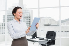 Cheerful businesswoman using table PC in office Stock Image