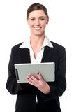 Cheerful businesswoman using tablet pc. Smiling female manager operating tablet device Royalty Free Stock Images