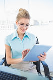 Cheerful businesswoman wearing glasses using tablet Royalty Free Stock Images