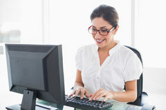 Cheerful businesswoman working at her desk Royalty Free Stock Photos
