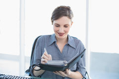 Cheerful businesswoman writing in her diary sitting at her desk Royalty Free Stock Photo