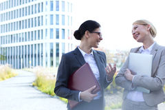 Cheerful businesswomen conversing while holding folder and laptop outside office building Royalty Free Stock Photos