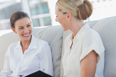 Cheerful businesswomen talking and working together Stock Photos