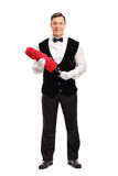Cheerful butler holding a red duster royalty free stock photo