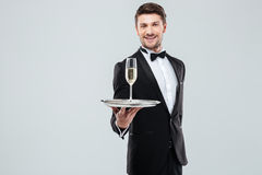 Cheerful butler in tuxedo offering you glass of champagne Stock Photography