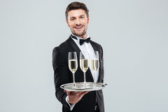 Cheerful butler in tuxedo smiling and offering champagne. Cheerful young butler in tuxedo smiling and offering champagne royalty free stock images