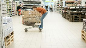 Cheerful buyer man riding on a cart among the products in the supermarket stock video footage