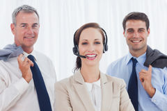 Cheerful call center agent posing with her work team Stock Image