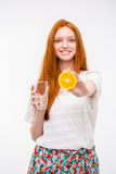 Cheerful candid redhead girl holding glass and offering orange Royalty Free Stock Photo