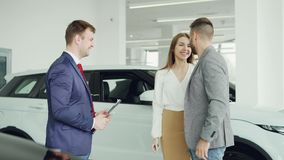 Cheerful car dealership salesman is shaking hands with young buyer handsome man then giving key fob to his happy wife. Couple is hugging and kissing stock video