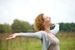 Cheerful carefree woman with arms outstretched. Close up portrait of a cheerful carefree woman with arms outstretched Stock Images