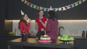Cheerful carefree women dancing on birthday party. Positive females in cone hats cklinking glasses, drinking champagne while performing funny dance during stock video