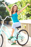 Cheerful Carefree Young Woman. Full length portrait of carefree young woman sitting on bicycle with arms out. Vertical shot Stock Images