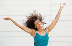 Cheerful carefree young woman. Portrait of a cheerful carefree young woman with arms raised Stock Images