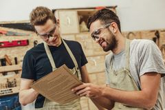 Cheerful carpenters reading specifications stock image