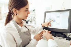Cheerful cashier using digital device for payment stock photos