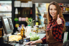 Cheerful cashier woman on workspace showing thumbs up. Picture of cheerful cashier woman on workspace in supermarket shop. Looking at camera showing thumbs up Stock Photos