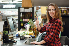 Cheerful cashier woman on workspace showing thumbs up. Picture of cheerful cashier woman on workspace in supermarket shop. Looking at camera showing thumbs up Stock Images