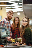 Cheerful cashier woman on workspace in supermarket. Picture of cheerful cashier women on workspace in supermarket shop. Looking at camera Royalty Free Stock Image