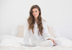 Cheerful casual brown haired woman in white pajamas sitting on her bed Royalty Free Stock Photos